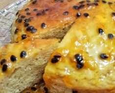 Um prato redondo de vidro com um bolo de maracujá sem glúten, com uma fatia a mostra, coberto com uma calda de maracujá com sementes;