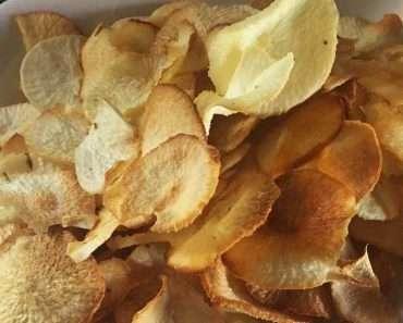 Chips de Mandioca Assado dentro de uma vasilha de plástico na cor branca.