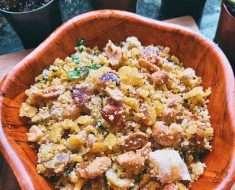 Uma vasilha de madeira em formato de flor com uma farofa de milho combinada com farofa de mandioca, amendoim e castanhas.