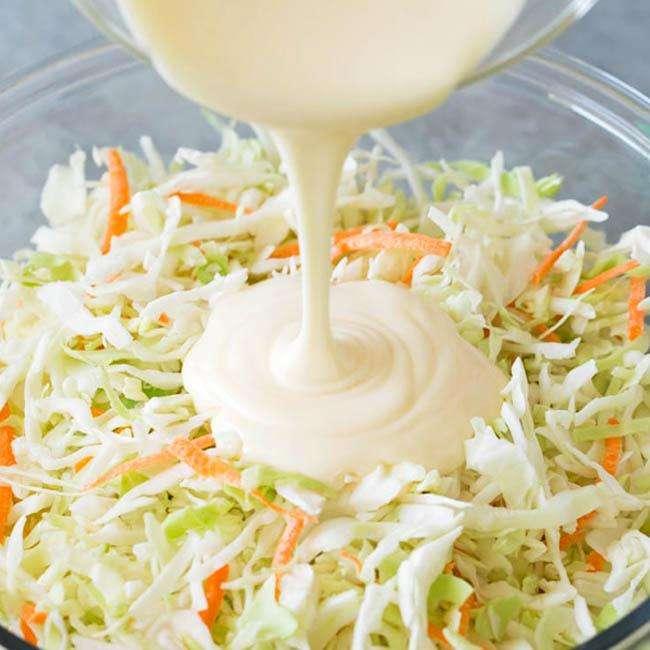 Um molho branco cremoso sendo despejado sobre uma salada de repolho dentro de uma travessa de vidro.