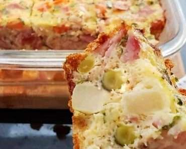 Omelete gigante feito com varios vegetais picados, queijo e presunto dentro de uma travesa retangular de vidro, sob uma tabua de madeira clara.
