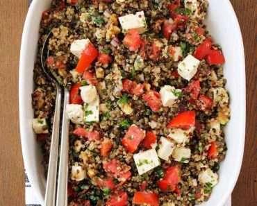 Uma salada de lentilha para o ano novo com quinoa, tomate e pedaços de queijo, servido dentro de uma travessa retangular branca, sob uma mesa de madeira.