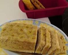Um bolo de banana fit rápido sob um prato branco com desenho azul e amarelo, uma forma vermelha de silicone no fundo com 2 bananas