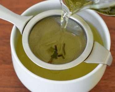 Uma xícara branca com uma peneira em cima, e uma chaleira despejando desinchá caseiro.